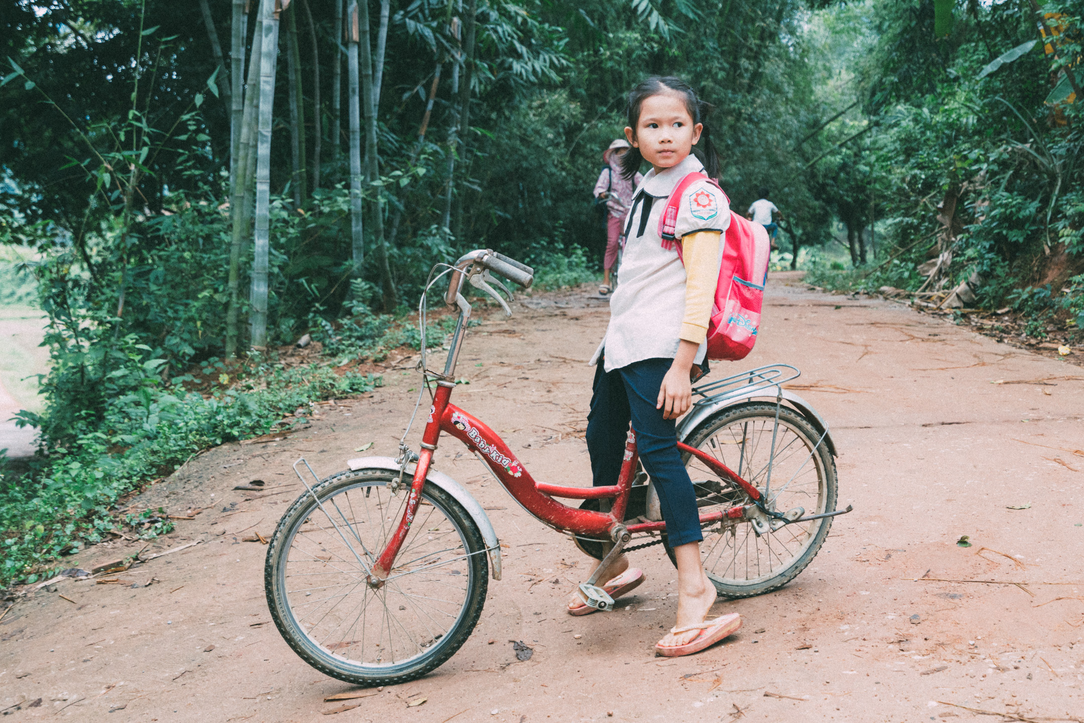 little girl and red bicycle